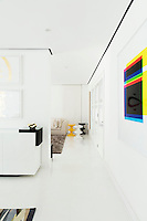 The dining room is separated from the sitting area by a partition wall. Vibrant accent colours found in artwork and other pieces breaks up the predominately white palette of the rooms.