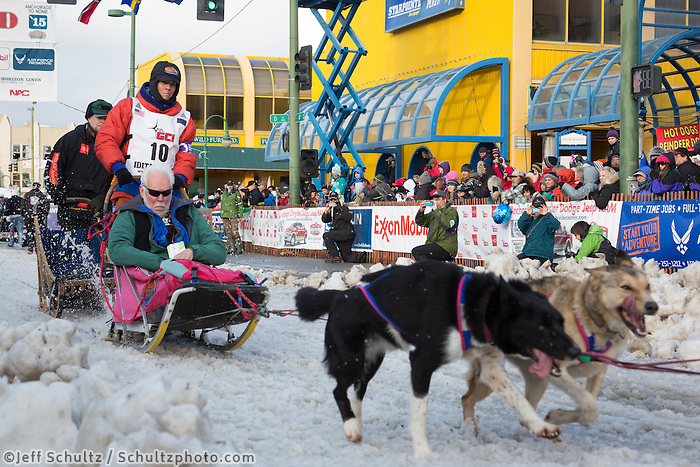 Cindy Abbott and team leave the ceremonial start line with an Iditarider at 4th Avenue and D street in downtown Anchorage, Alaska during the 2015 Iditarod race. Photo by Jim Kohl/IditarodPhotos.com