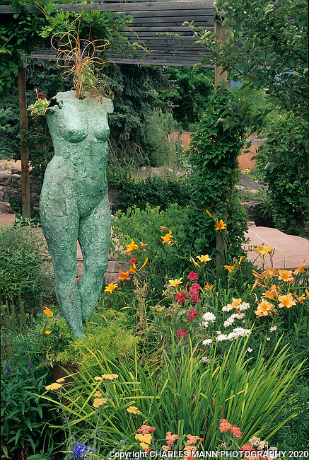 A statue of Venus, planted with some ornamental grass, reigns over the  perennial garden of Elspeth Bobbs in Santa Fe, New Mexico