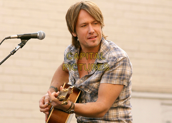 KEITH URBAN.is joined by Verizon Wireless and Samsung Mobile as he makes an in-store appearance for his fans at the Verizon Wireless store in Pasadena, California, USA, November 21st 2009                                                                   .half length music concert gig live on stage grey gray brown plaid checked check shirt microphone playing tattoo bracelets guitar .CAP/RKE/DVS.©DVS/RockinExposures/Capital Pictures