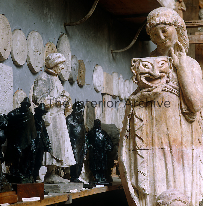 In the atelier of the Henri Bouchard Museum a smiling neo-classical plaster muse is displayed next to a collection of bronze and plaster figurines