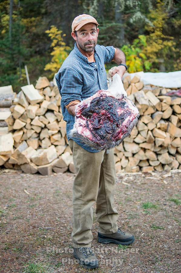 Outdoor Life Editor Andrew McKean holds up meat cut from mule deer after a kill while hunting on Greyback Ridge in the Hoeback Drainage of Wyoming Region H, outside of Alpine, Wyoming, Thursday, September 24, 2015. <br /> <br /> Photo by Matt Nager