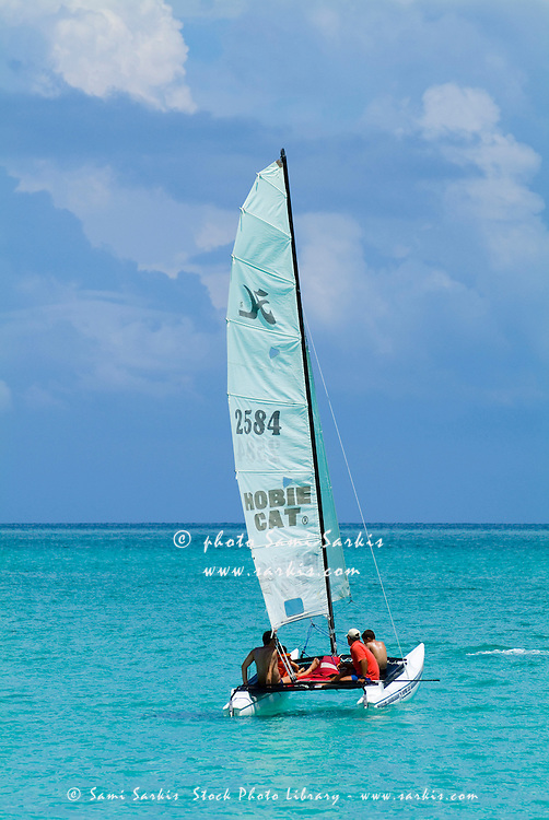 Family going for a ride in a sailboat in the blue waters of Cayo Santa-Maria, Cuba.