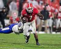 ATHENS, GA - OCTOBER 19: D'Andre Swift #7 of the Georgia Bulldogs evades a tackle by Joshua Paschal #4 of the Kentucky Wildcats during a game between University of Kentucky Wildcats and University of Georgia Bulldogs at Sanford Stadium on October 19, 2019 in Athens, Georgia.
