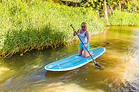 Blonde woman with sunglasses kneels while stand up paddleboarding on the Hanalei River, Kaua'i