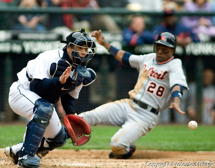 Detroit TIgers' Curtis Granderson, right, safely slides past Seattle Mariners Kenji Johjima, of Japan, to score in the third inning of Major League Baseball game in Seattle on Sunday, June 1, 2008. Granderson scored on Carlos Guillen double down the right field line. (AP Photo/Jim Bryant)..