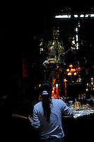 Female devotee with burning incense sticks. Taoist temple; the Emperor Jade Pagoda (Chua Ngoc Hoang or Phuoc Hai Tui); Ho Chi Minh City (Saigon); Vietnam