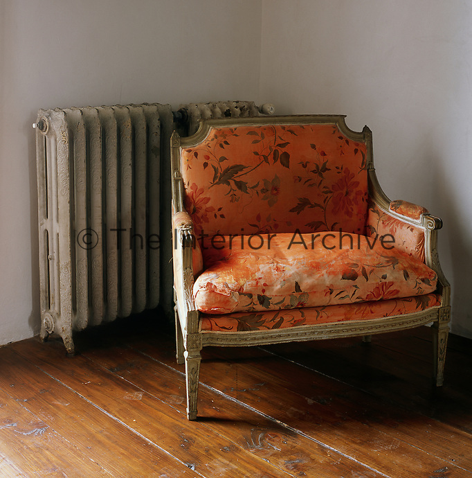 An Empire armchair upholstered in an orange, floral pattern fabric stands in one corner of a room.