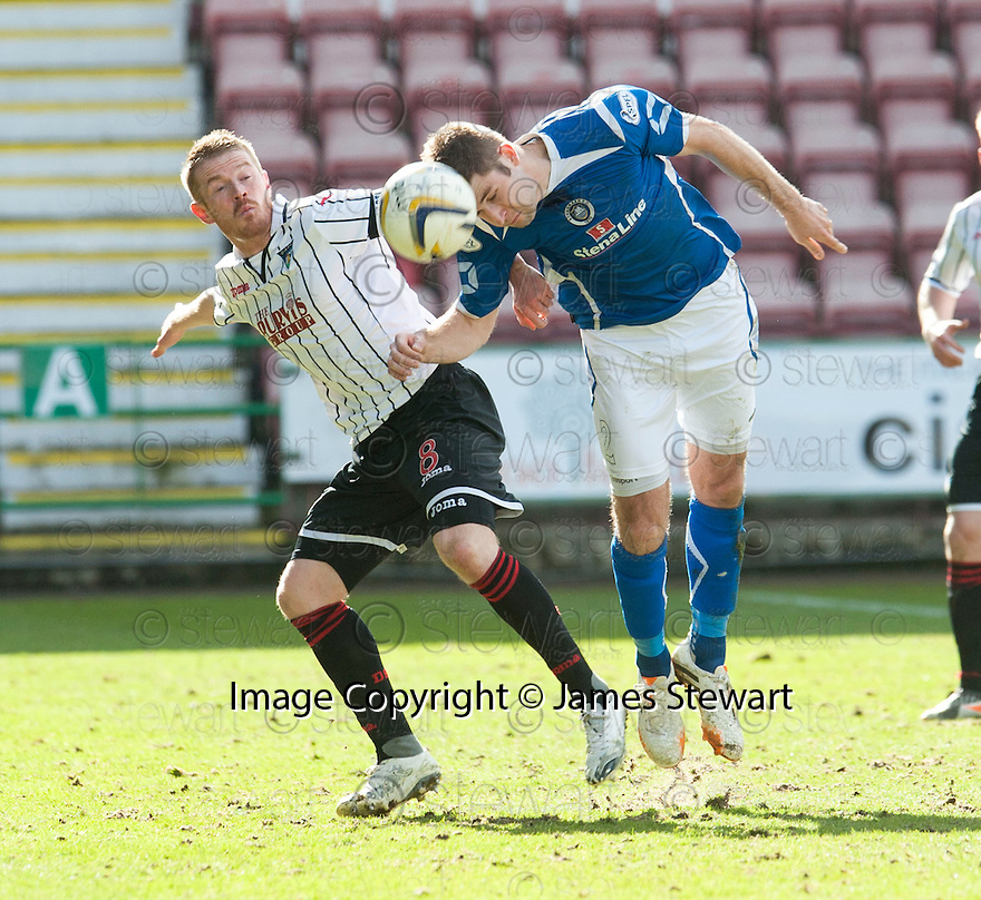 Pars' Andrew Geggan and Stranraer's Craig Pettigrew challenge for the ball.
