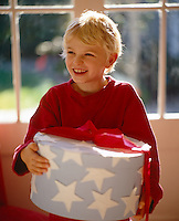 A smiling boy carrying a large present decorated with cut out stars and tied with a bright red ribbon