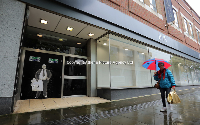 Pictured: A woman walks past a poster of Sir Philip Green on the door of the now closed down BHS store in Oxford Street, Swansea, Wales, UK. Tuesday 13 September 2016<br /> Re: Former owner of BHS, Sir Philip Green has paid a surprise 'visit' to the closed down BHS store in Swansea.<br /> He was spotted in the doorway of the Oxford Street store, which closed its doors for the last time last month.<br /> In his hand was a BHS shopping bag with money spilling out of it.<br /> Sir Philip had owned BHS before selling it for &pound;1 last year.<br /> He is claimed to have taken millions out of the company in dividends and left behind a &pound;571m pensions deficit.<br /> Alongside the poster are the words: &quot;Thankyou for your custom Sir&quot;.