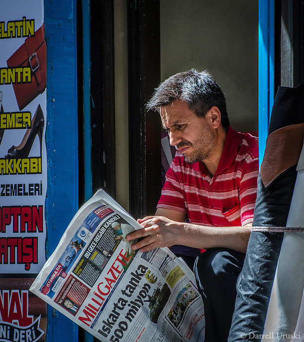 Urban Street Photograph of a person reading the MilliGazette News in Istanbul Turkey.