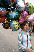 Woman selling a bunch of decorative balloons. Grand Old Day Festival. St Paul Minnesota MN USA
