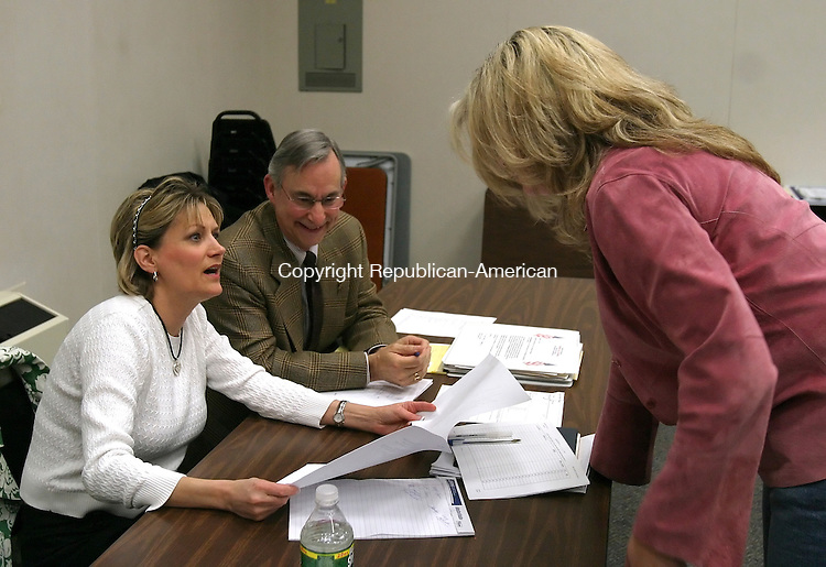SOUTHBURY, CT 03/31/08- 033108BZ02- From left- Lora Morrow, vice chair of the Southbury Republican Town Committee, Roger Giordano, treasurer, and Jennifer Naylor, an elected delegate for the congressional race, finalize delegate certification paperwork after a caucus to elect the delegates Monday.<br /> Jamison C. Bazinet Republican-American
