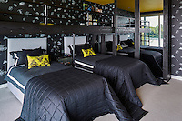 The combination of dark grey soft furnishings with touches of citrus yellow create a dramatic feel to a child's bedroom. The black wallpaper and the cushions have an insect motif. A mirror wall creates the illusion of space.
