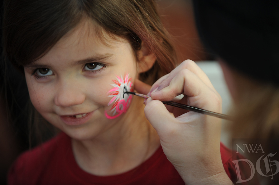 NWA Media/ANDY SHUPE - Ally Vaughan, 6, of Greenland smiles Sunday, Jan. 4, 2014, as her face is painted by artist Mary Munford before the University of Arkansas women's basketball game with Texas A&M in Bud Walton Arena in Fayetteville.