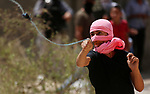 A Palestinian protester uses a slingshot to hurl stones towards Israeli forces during clashes following a weekly demonstration against the expropriation of Palestinian land by Israel in the village of Kfar Qaddum, near the West Bank city of Nablus on September 7, 2018. Photo by Shadi Jarar'ah