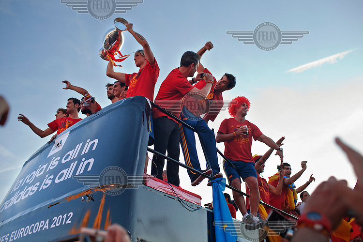 Fernando Torres holds up the Henri Delaunay trophy during the victory parade of the Spanish national football team who won the UEFA EURO 2012 competition.