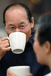 Asian man drinking coffee at cafe