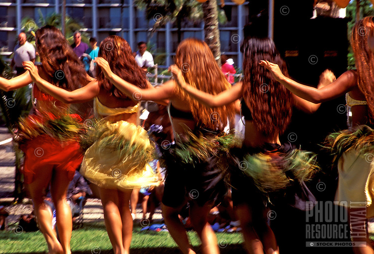 Back view of a row of Tahitian dancers with their arms extended and their skirts in a blur from their fast-moving hips, Hilo, Big Island.