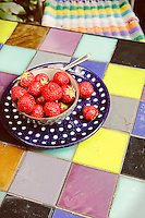 A dish of fresh strawberries on the colourful tiled top of a garden table designed by Therese Thoreux