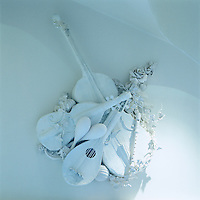 Close up of a plaster wall ornament inspired by a collection of string instruments