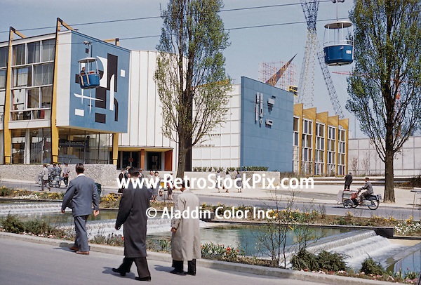 1958 Brussles Worlds Fair building with people walking by the fountain stream. Overhead cable cars.