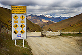 A warning sign at the entrance to the Skippers road with a view over Long Gully towards Mount Aurum, Queenstown Lakes District, Otago, South Island, New Zealand.