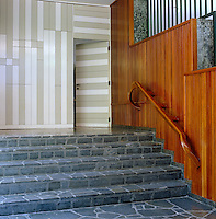 The front entrance to the Beracasa villa designed by Italian architect Gio Ponti in the late 1950s with wood panelled walls and a stone staircase
