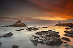 A lighthouse and wave action at sunset on the rocky shore just south of Pigeon Point, Central California, USA.