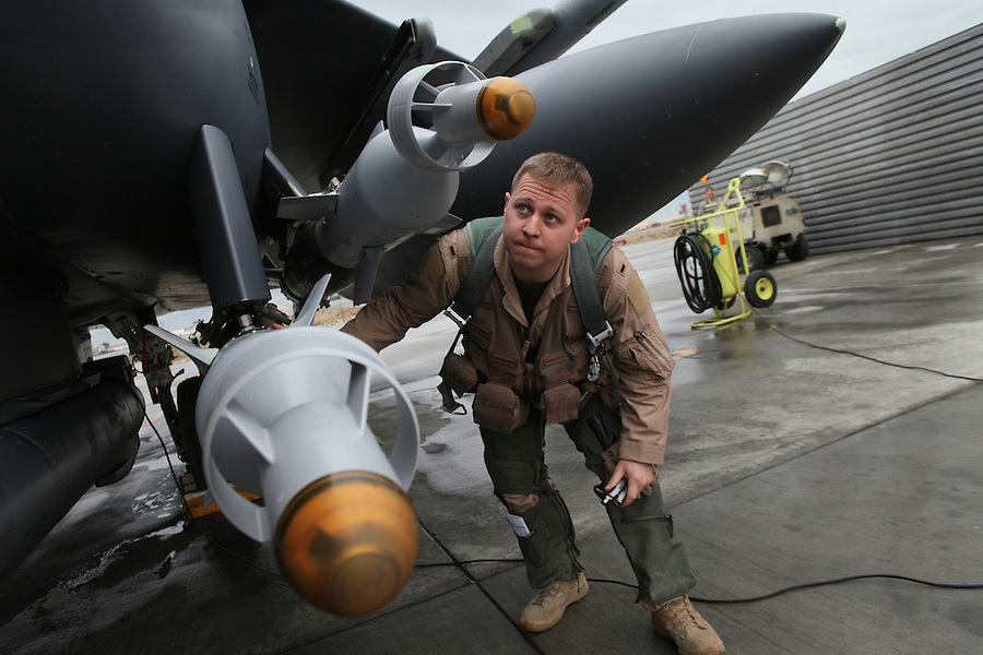 An Air Force pilot with the 455th Air Expeditionary Wing at Bagram Air Force in Afghanistan checks the laser-guided munitions attached to the wings and fuselage of his F-15 fighter before departing on an air combat patrol on Thursday April 10, 2009. Air strikes linked to civilian deaths have caused increasing tension in the relationship between the Afghan people and foreign militaries operating in their country.