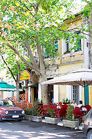 A street in central part of town with restaurants and cafes with outside seating terrace under trees giving shade. Podgorica capital. Montenegro, Balkan, Europe.