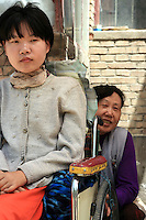 Li Yan sits in her wheel-chair while her mother Song Fengying seats behind it, outside their house in Yinchuan, Ningxia Province, China, on May 7, 2007. 28-year-old Li Yan suffers from motor neuron disease also known as amyotrophic lateral sclerosis (or ALS), the same illness that has thereotical physicist Stephen Hawking. Li Yan asked China's National People's Congress (NPC) to consider a draft on euthanasia. Photo by Lucas Schifres/Pictobank