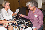 Two senior women look at photos from high school at reunion