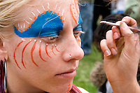 Teen age 16 having face painted in preparation for the parade. MayDay Parade and Festival. Minneapolis Minnesota USA