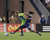 New England Revolution midfielder Shalrie Joseph (21) tackles Seattle Sounders FC forward Roger Levesque (24). The New England Revolution defeated the Seattle Sounders FC, 3-1, at Gillette Stadium on September 4, 2010.