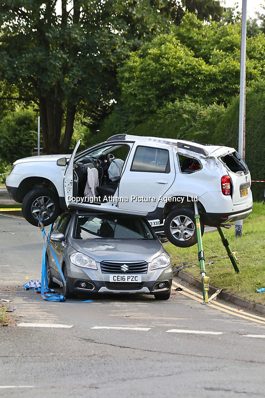 """Pictured: The scene of a car collision in which a white Dacia Duster was left balancing on top of a grey Suzuki in Newport, Wales, UK.<br />Re: A two-car crash in a residential area of Newport, south Wales, left one car balancing on top of the other next to a busy roundabout.<br />The accident happened on Saturday afternoon near Barrack Hill.<br />A white Dacia Duster was left perched on top of a grey Suzuki car next to Harlequin roundabout. Both cars suffered serious damage.<br />Harlequin roundabout and Queen's Hill close in both directions as a result of the accident.<br />Photographer Andrew Morgan Evans, 35, from Newport, was on his way home from a shopping trip when he noticed the crash scene.<br />He said: """"I had never seen anything like it. People passing by were stopping to look and took photos on their phones.<br />""""The police road collision unit were there.""""<br />There was smashed glass spread across the road.<br />""""I just kept wondering 'how did a car land on top of another?',"""" Mr Evans added."""