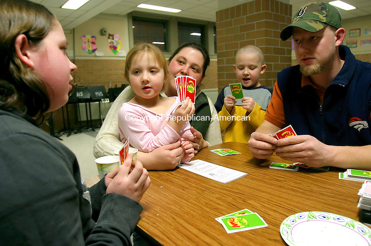 NAUGATUCK, CT- 27 MARCH 2008 --032708JS06--Norma Weston, third from left and her husband Ken Weston, right, play the card game Apple to Apple with their children Haley Lester, 12, left, Lilly Weston, 4, second from left and Kenny Weston, 6, during the annual Family Game Night Thursday at Hop Brook Intermediate School in Naugatuck. The game night was organized by Brenda Goodrich, a reading specialist at the school who wanted promote time between children and their parents. More than 160 children and parents participated in Thursday's event. <br /> Jim Shannon / Republican-American