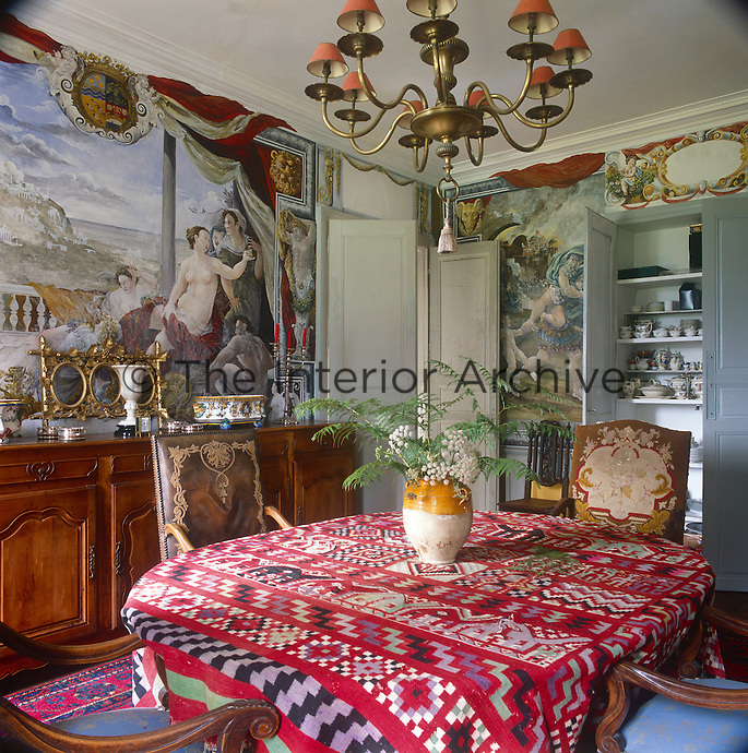 A brass chandelier hangs above a dining table and upholstered dining chairs. The tablecloth has a kilim pattern in red. The walls are decorated with painted murals.