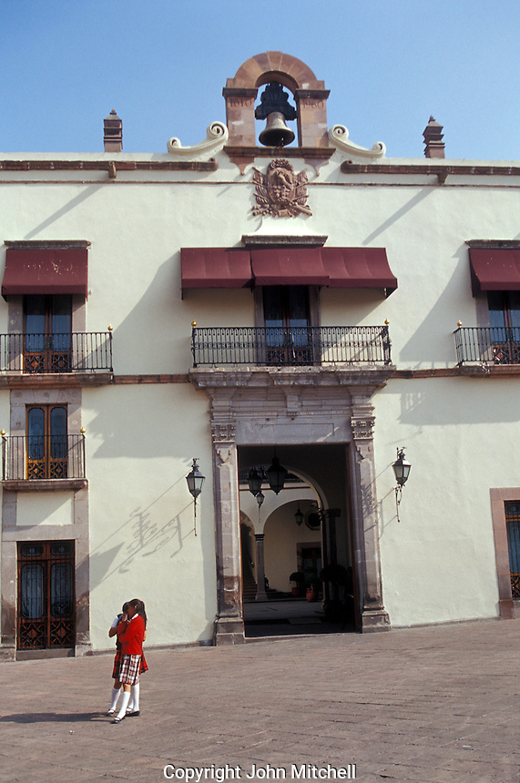 Two school girls standing in front of the Palacio de Gobierno or Casa de la Corregidora in the city of Queretaro, Mexico. The historic centre of Queretaro is a UNESCO World Heritage Site.