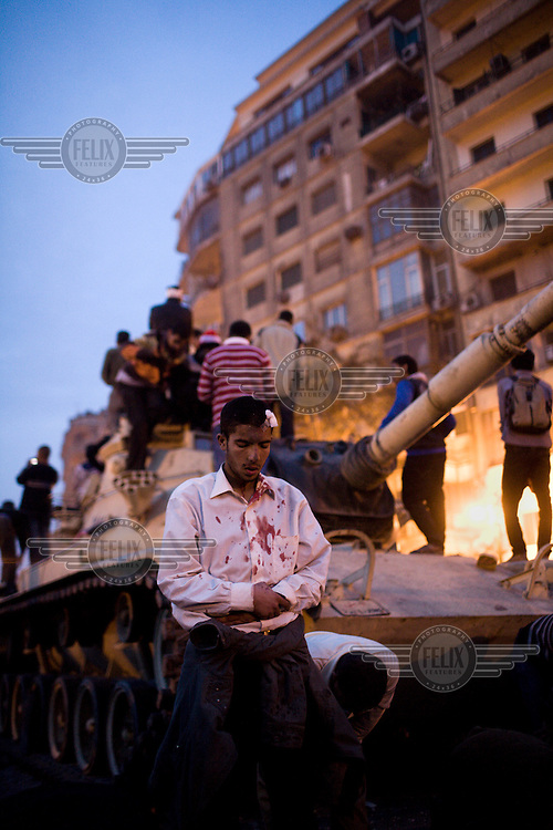 An injured anti-government protester prays in front of a tank in Tahrir Square following hours of bloody street battles between pro and anti-government factions. 25 January 2011 saw the beginning of a nationwide 18 day protest movement that eventually ended the 30-year rule of Hosni Mubarak and his National Democratic Party.
