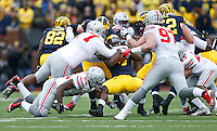 Ohio State Buckeyes defensive lineman Michael Hill (77), defensive lineman Tyquan Lewis (59) and defensive lineman Joey Bosa (97) tackle Michigan Wolverines running back De'Veon Smith (4) during the NCAA football game at Michigan Stadium in Ann Arbor on Nov. 28, 2015. Ohio State won 42-13. (Adam Cairns / The Columbus Dispatch)