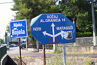 A road sign in Tuzi pointing to Hoti and Mataguzi and Bozaj and the border to Albania straight ahead. Rijeka Rujela river. Montenegro, Balkan, Europe.