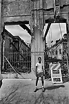 A young child stands in front of a riot damaged building on W. Adams Blvd. in South Los Angeles.