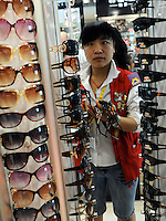 """Fake Doce and Gabanna sunglasses sale at the silk Market. The """"Silk Market"""" in Central Beijing is proving a major tourist attraction with thousands of Olympic tourists flocking there daily in order to purchase fake designer goods ranging from clothing to watches.  The Beijing authorities closed hundreds of night-clubs and introduced many restriction on and rules ahead of the 2008 Olympics in the city mysteriously has allowed the trade of fake goods to foreigners continue, thumbing their nose at western companies.<br /> <br /> Photo by Richard Jones / sinopix"""