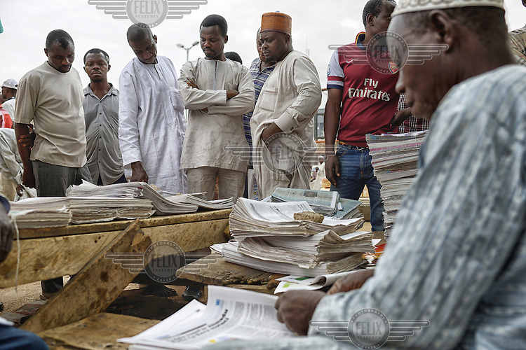 A group of men gather around a newspaper seller's stall to read the latest results from the 2015 Presidential elections. Initial results indicated a tight race but as the counting of votes progressed it soon became clear that Muhammadu Buhari, leader of the APC (All Progressives Congress Party), had prevailed.