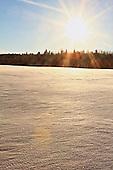 sun setting over a field in winter