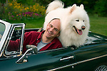 mature male with his husky dog in MG sports car
