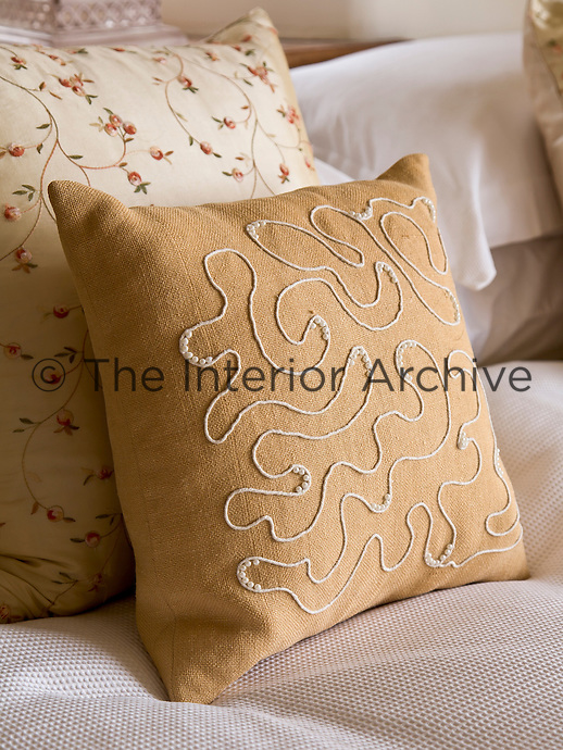 Matching pairs of cushions decorate the bed in the master bedroom