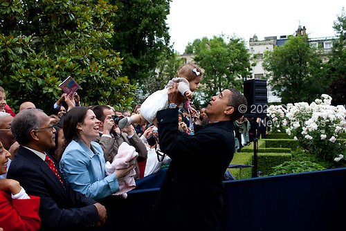 Caen, France - June 6, 2009 -- United States President Barack Obama lifts a baby while meeting the staff of the U.S. Embassy after arriving at the ambassador's residence in Caen, France, Saturday, June 6, 2009. .Mandatory Credit: Pete Souza - White House via CNP